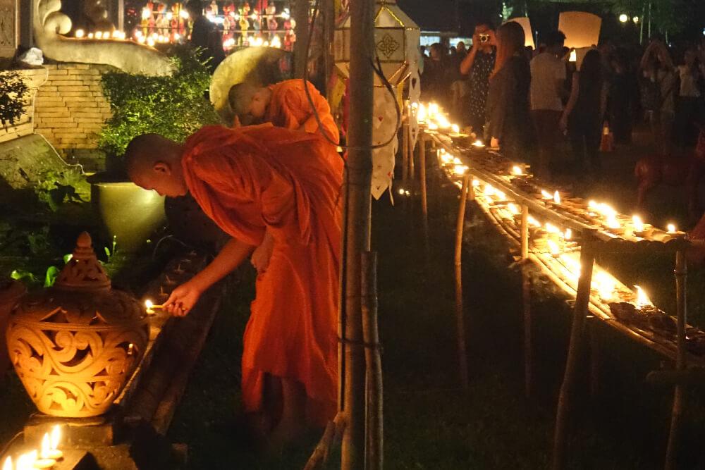 Buddhistische Moenche zuenden Kerzen an