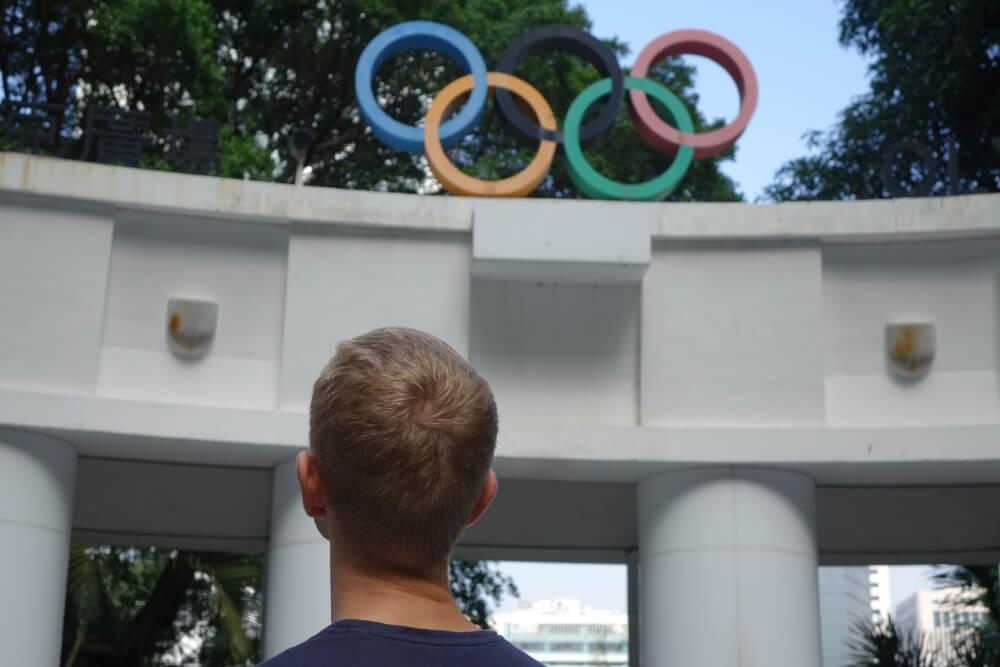 Die 5 Olympia Ringe auf dem Olympia Monument in Hong Kong ueber dem Kopf von Henning Roxin