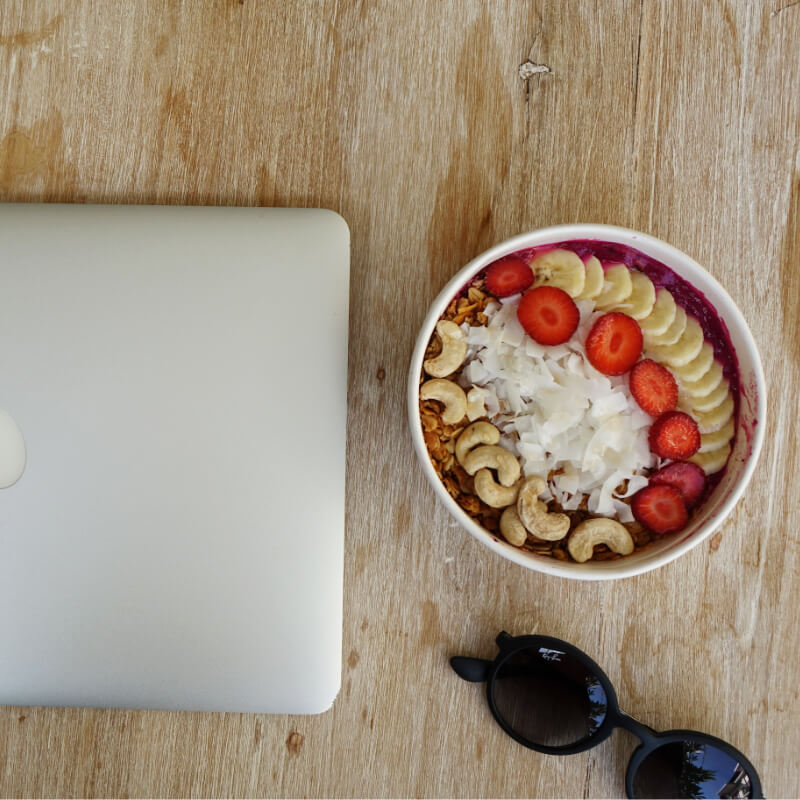 Tropische Smoothiebowl auf Holztisch, Macbook, Sonnenbrille
