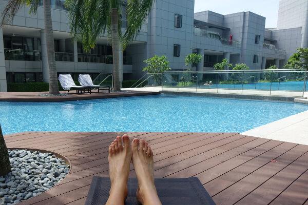 Leben in den Tropen: Blick auf die eigenen Fuesse und den Pool, Singapur