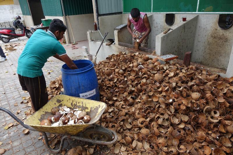 Verarbeitung der Kokosnuesse bei einem Billigproduzenten: auf dem Parkplatz, ohne Sicherheitskleidung, ohne Hygienemassnahmen