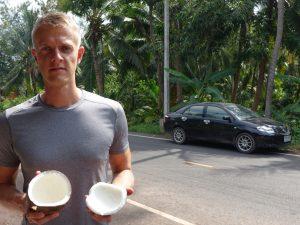 Henning Roxin auf Kokosöl Plantage mit einer aufgeschlagenen Kokosnuss