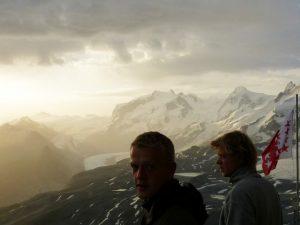 Sonnenaufgang auf einem Gipfel der Schweizer Alpen mit zwei jungen Maennern