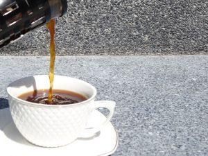 Kaffee wird aus einer French Press in eine Tasse gegossen